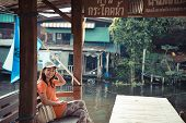 Cute Asian Thai Girl Is Relaxing In The Pavilion Near He Riverside In Vintage Color Style.