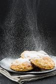 picture of sprinkling  - Sprinkling powdered sugar on cakes on a black background