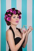 retro pin up girl spraying perfume with hair rollers and makeup.