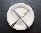 Silver cutlery  and vintage plate on a dark grey background.