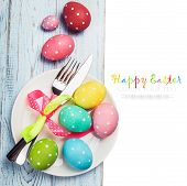 Colorful Easter Eggs And Cutlery On A White Background