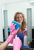 Smiling Woman Cleaning A Mirror In A Bathroom
