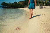 Woman Walking Past A Starfish On Beach