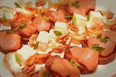 Various snacks with soft cheese and salmon in plate on banquet table, toned image