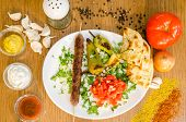 Plate of traditional kebab with meat, fried potatoes, tomato, dressing, perper and garlic