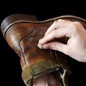 The shoemaker puts shoe polish on black background
