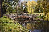 Stone Bridge Across The Lake In A Park In Spring