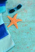 Summer concept with beach towel, starfish and sunglasses on grunge table
