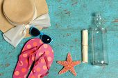 Vintage table with Summer items such as hat, sunglasses, flip-flops, starfish and message in a bottle