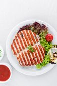 Grilled fillet chicken served with tomatoes and roast vegetables