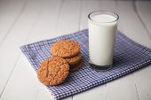 Oatmeal Cookies And Glass Of Milk On Napkin On White Table