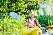 woman with kayak or canoe on forest river