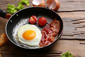 Bacon and eggs on rustic wooden planks background