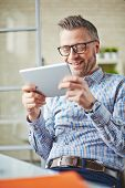 Smiling businessman in eyeglasses reading information in touchpad