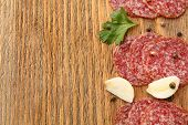 Slices of salami with cloves of garlic and spices on wooden background