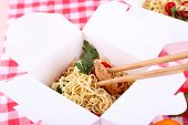 Chinese noodles and sticks in takeaway box on fabric background