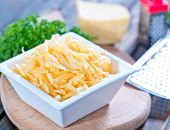 image of grating  - grated cheese in bowl and on a table - JPG