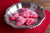 Cookies in form of heart on metal tray and napkin on wooden table background