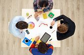 Top view table with creative people and gadgets