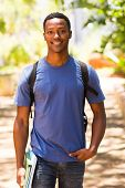 good looking male african college student walking on campus