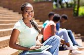 portrait of african college girl sitting on steps