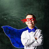 school boy wearing a superhero costume with blackboard behind him