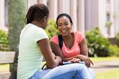 cheerful african female students sitting on bench at university campus