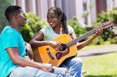 beautiful african girl playing guitar for her boyfriend