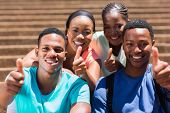 group of cheerful african friends giving thumbs up