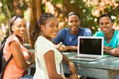 group of african college student relaxing outdoors and looking at the camera