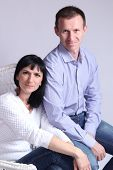 Middle aged couple posing in a white lounge chair
