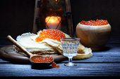 Pancakes With Red Caviar And A Wine-glass Of Vodka And An Old Lantern
