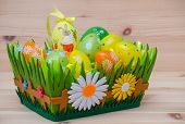 happy easter bunny with eggs in a basket and flower on the wooden background