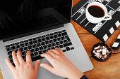 Female hands of scriptwriter working on laptop at wooden desk background