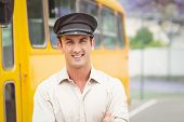 stock photo of bus driver  - Smiling bus driver looking at camera outside the elementary school - JPG