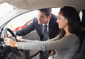 pic of driver  - Happy female driver at the wheel sitting in her car at new car showroom - JPG
