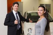 Businessman showing a car to a woman at new car showroom