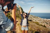 picture of young woman posing the camera  - Happy young woman posing with her arms raised to her boyfriend taking her photos with digital camera - JPG