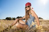 stock photo of tallgrass  - Beautiful hippie girl sitting on a meadow  - JPG