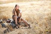 image of tallgrass  - Hippie girl sitting on a tree stump - JPG