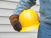 picture of denim wear  - Closeup of man holding hardhat with house siding background - JPG