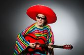 stock photo of sombrero  - Man in red sombrero playing guitar - JPG
