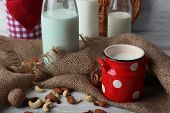 stock photo of sackcloth  - Milk in glassware and walnuts on wooden table with sackcloth - JPG
