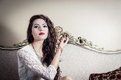 stock photo of mystique  - Pretty model girl wearing white dress sitting on victorian sofa posing for camera with artistic facial expression - JPG