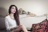 picture of bolivar  - Pretty model girl wearing white dress sitting on victorian sofa looking out in the room - JPG
