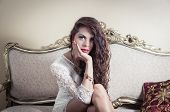 image of bolivar  - Pretty model girl wearing white dress sitting on victorian sofa posing for camera with bored facial expression - JPG