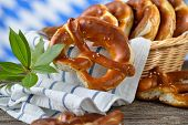 image of pretzels  - Fresh Bavarian pretzels in a breadbasket on a wooden table - JPG