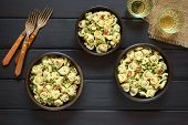 pic of dark side  - Tortellini salad with green peas fried bacon and parsley served in rustic bowls with forks and glasses of white wine on the side photographed overhead on dark wood with natural light - JPG