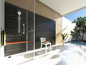 picture of shower-cubicle  - Simple glass shower cubicle in a modern bathroom with grey accent wall and white parquet floor leading to a walled outdoor patio with tree and potted plants - JPG