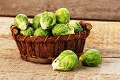 foto of brussels sprouts  - Basket of fresh green brussels sprouts on wooden background - JPG